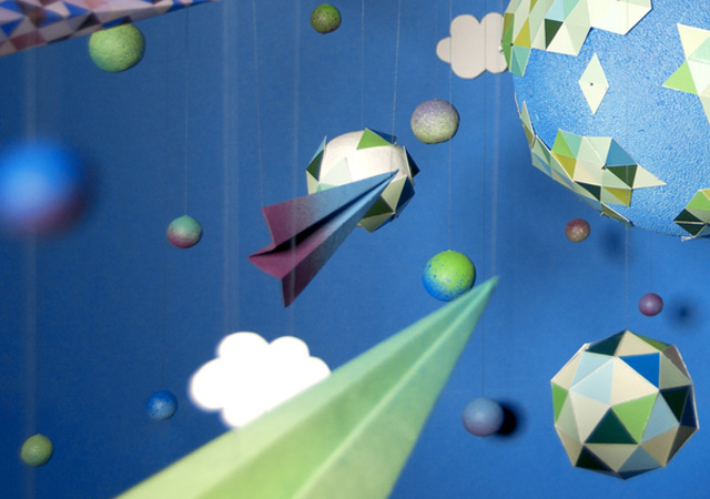 paper planes flying through paper clouds towards a big paper planet