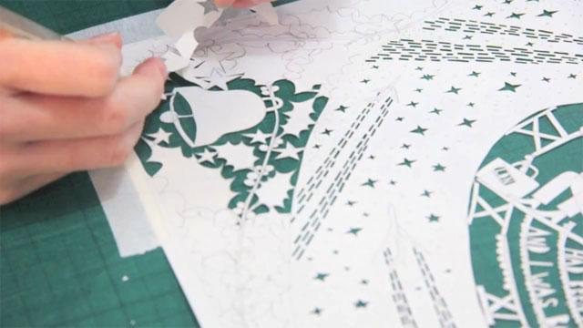 Rob Ryan - paper cutting the Heathrow Christmas card